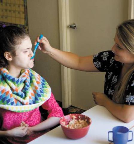 Caregiver feeding a special child
