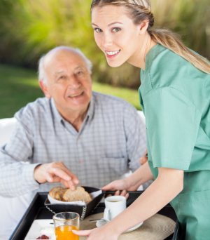 Nurse giving meal to a senior